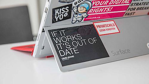 Laptop mit bunten Aufklebern im Coworking Space