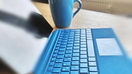 Blauer Laptop mit Tastatur und Tasse